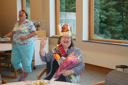 "Carla Tracy, Library Director, gives a royal wave after being crowned ""Queen of the Library.""  She has a crown and sash made of recycled book jackets."