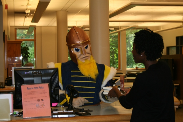 Gustav Mauler is happy to help students returning their library materials!